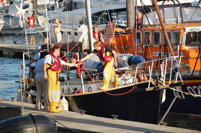 Home safe and sound - and on dry land. Crew Member Joe Manning handing the mooring line to Glen Mallen to the yacht can be tied up alongside in Poole Quat Boat Haven. 22 August 2013 Photo credit: RNLI/Dave Riley22 August 2013.  Photo credit: RNLI/Dave Riley