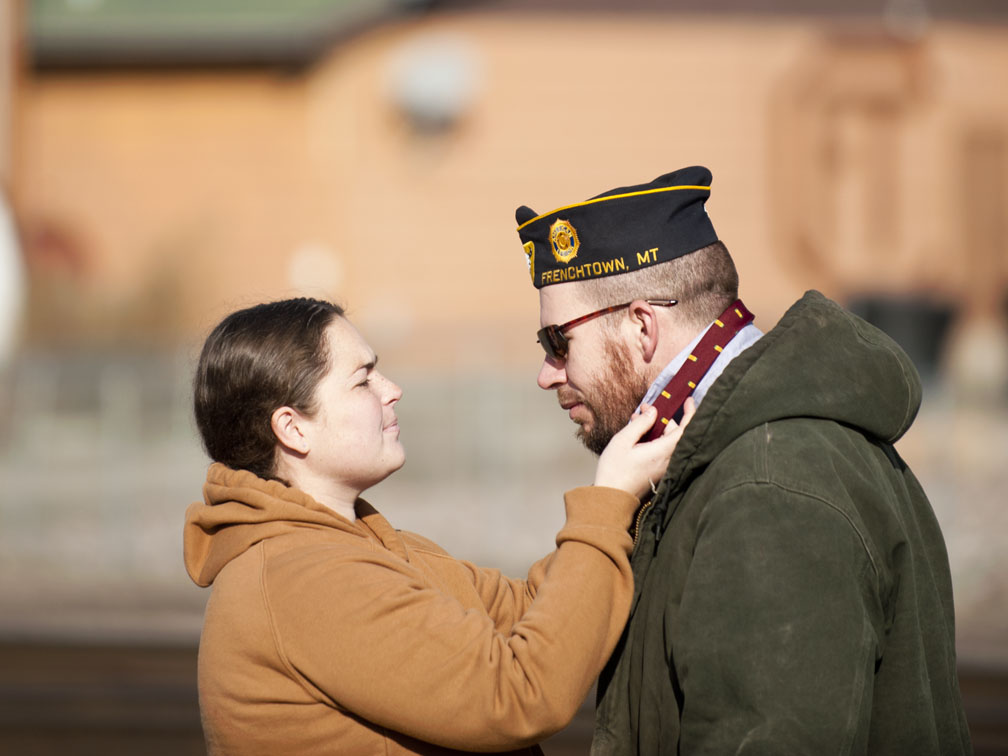 Natalie Thurman helps her husband, Tim, with his tie after the Veterans' Day Ceremony in Frenchtown. Tim Thurman served in Iraq from 2003 to 2004. They have a baby on the way. Photo by Nate Ford.