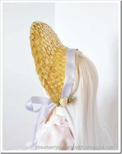 The side view of a doll wearing a half bonnet.