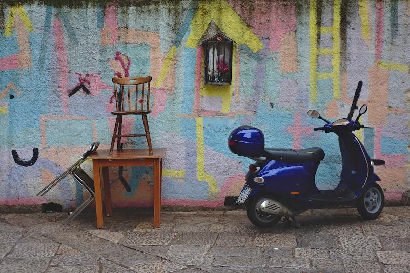 Scaune ramase in strada dupa petrecerea de sambata, scutere, grafiti si religie. Palermo.