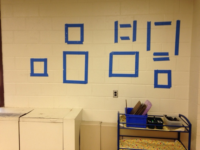 Use painter's tape in a slightly smaller shape than the poster to affix it to classroom walls.