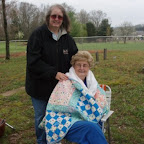 Dollie Blazek wraps Hilda in the picnic quilted tablecloth.
