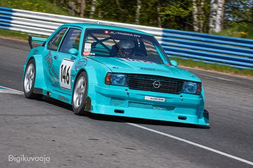 sininen Opel kovassa vauhdissa kilparadalla