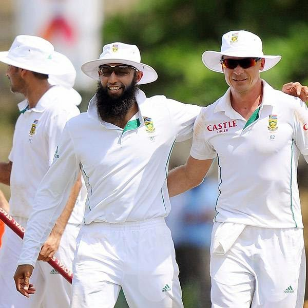 South African cricket captain Hashim Amla (C) celebrates with teammate Dale Steyn (R) after victory in the opening Test match between Sri Lanka and South Africa at the Galle International Cricket Stadium in Galle on July 20, 2014. South Africa won the first Test against Sri Lanka by 153 runs on the fifth and final day in Galle.