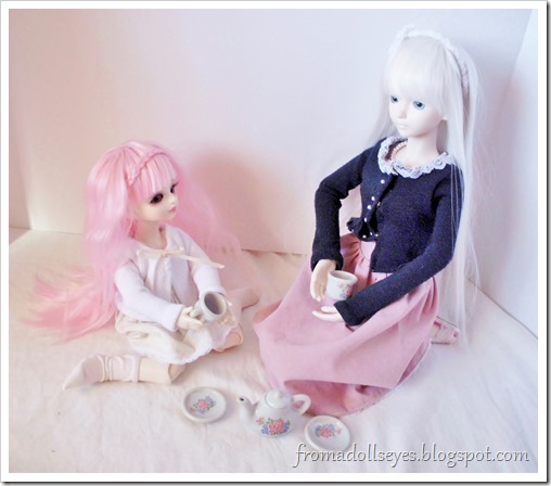 Two ball jointed dolls having a tea party.
