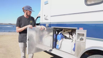 man showing storage in ambulance tiny home