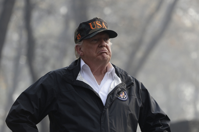 Trump scowls as he visits visits a neighborhood impacted by wildfires on Saturday, 17 November 2018, in Paradise, California. He denied any connection between global warming and the California wildfires, saying 'I want great climate, we're going to have that.' Photo: Evan Vucci / AP Photo