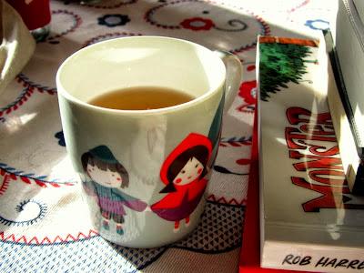 Mug of tea besides pile of books