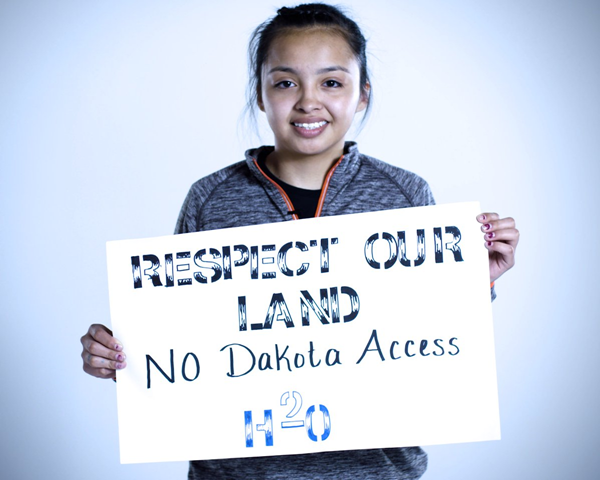 Tariq Brown Otter holds a sign that reads, 'Respect Our Land - No Dakota Access', to protest the Army Corps of Engineers issuing a construction permit that allows Dakota Access LLC to build a massive oil pipeline through Standing Rock Sioux land. Photo: Last Real Indians