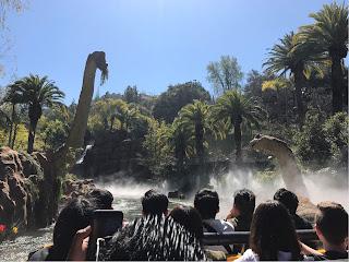 Utsikt fra en båt over en elv hvor to dinosaurer beiter langs kanten.