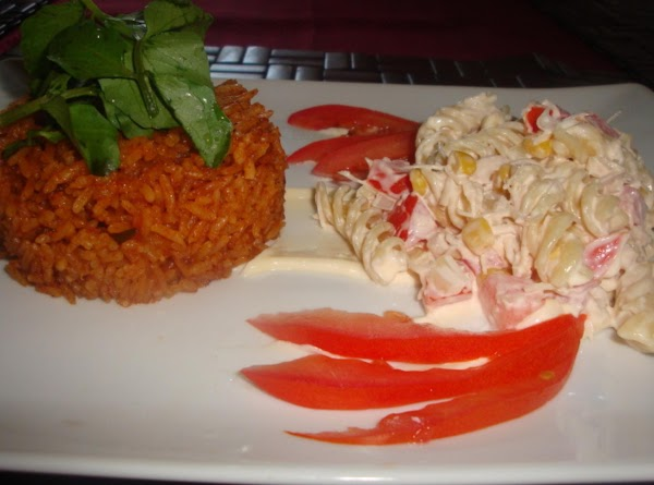 Herbed rice Jollof with Pasta and chicken salad, garnished with tomatoes
