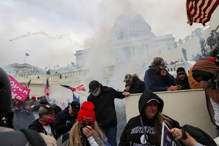 Supporters of US President Donald Trump cover their faces to protect themselves from teargas during a clash with police officers in front of the US Capitol building in Washington, U.S., January 6, 2021.