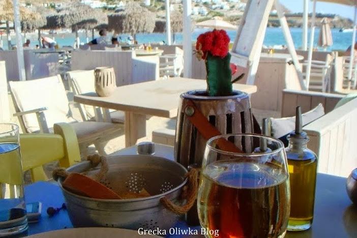 białe stoliki na greckiej plaży na stoliku lampka wina, pirczywo donica z wkwitnącym na czerwono kaktusem