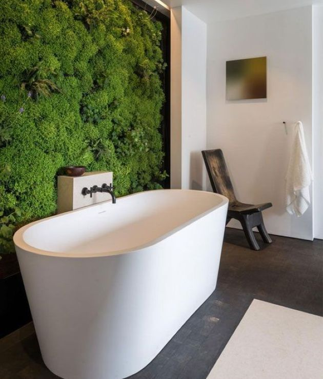 modern 2020 bathroom design with white freestanding tub and large green moss wall