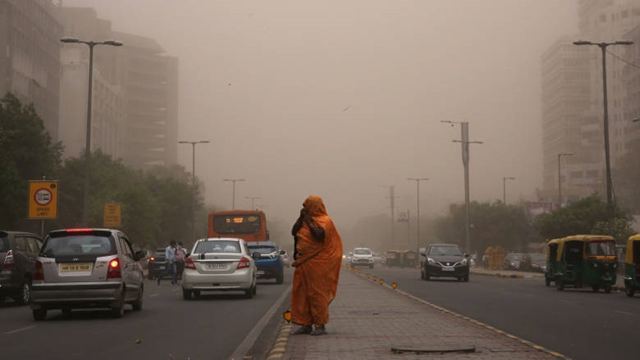 A woman walks with her face covered on Wednesday, 2 May 2018 to avoid a dust storm in New Delhi, located between Rajasthan and Uttar Pradesh. Northern India has been hit by powerful storms that have led to fatalities and damage to houses. Photo: Rajat Gupta / EPA-EFE