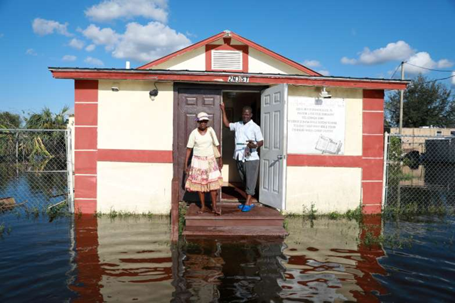 Pastor Louicesse Dorsaint stands with his wife Maria Dorsaint in front of their church, Haitian United Evangelical Mission, which was damaged by flooding from Hurricane Irma in Immokalee, Florida, on 12 September 2017. Photo: Stephen Yang / Getty Images