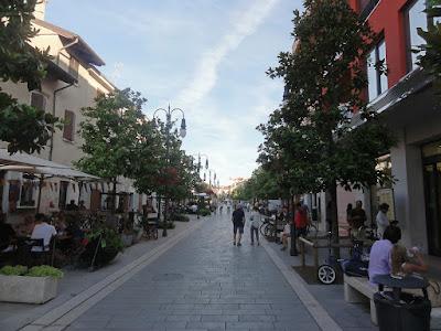 En bred gågate med butikker å begge sider.