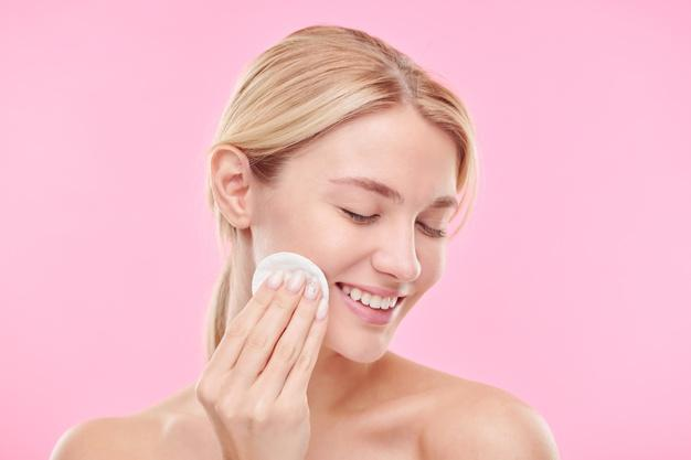 Pretty young smiling female with cotton pad enjoying procedure of cleaning face with toner or micellar water Premium Photo