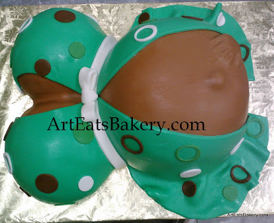 Green, white and brown custom baby bump baby shower cake with polka dots, bow and hand in belly