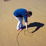 Passeio e desenhos com gravetos na praia