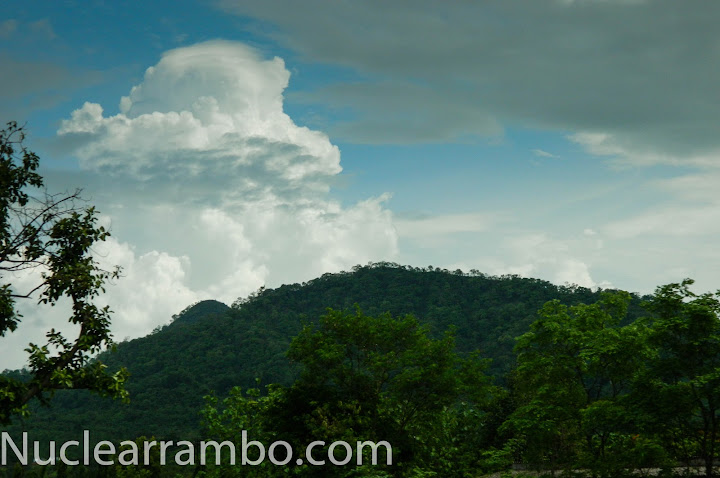 Cumulonimbus clouds behind hills