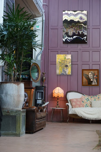 Paintings hung on purple wall of eclectic living room