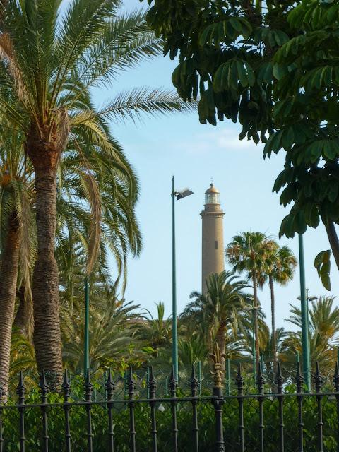 Der Leuchtturm von Maspalomas, durch ein paar Palmen und Bäume hindurch aufgenommen