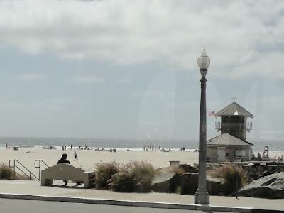 En strand med noen få mennesker og et lite tårn.