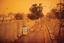 zwaar beschermde toegang tot gebouw van de The New York Times in Bagdad: hoge muren met prikkeldraad langs een weg met om en om links-rechts betonblokken op de weg. Een bewaker zit in zijn hokje bij een slagboom