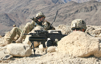 Photo: NURISTAN PROVINCE, Afghanistan - U.S. Army Sgt. Craig Foster, left, an infantry team leader from Clarion, Iowa, and U.S. Army Pfc. Brian Wisor, right, an infantry gunner from Ackley, Iowa, both Soldiers with Company C, 1st Battalion, 133rd Infantry Regiment, look from a ridge into the town of Tupac, Afghanistan, Jan. 21. Soldiers from Co. C, joined Afghan National Army Soldiers from Weapons Company, 1st Battalion, 201st Infantry Corp, on the patrol. After seven hours of dismounted searching through rugged terrain, Co. C and their Afghan counterparts located an improvised explosive device along Route Iowa, thanks to a tip from someone in the area of Tupac, Afghanistan. The Soldiers had been struck by an IED in Tupac two days earlier. Fortunately, no U.S. or Afghan Soldiers were injured in the attack. After locating the IED, the Soldiers then walked back to Forward Operating Base Kalagush, hiking about eight miles up and down mountains for the day. (Photo by U.S. Army Staff Sgt. Ryan C. Matson, Task Force Red Bulls Public Affairs Office)