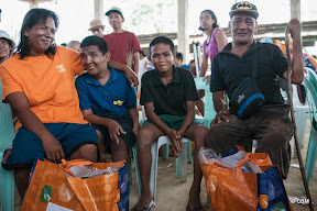 A man, woman, and two boys smiling with two orange bags