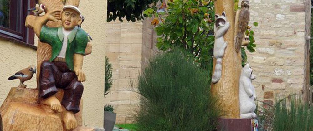 Schnitzerei - Figuren im Vorgarten der Familie