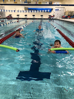 Two athletes swimming in lanes in the follow, followed by coach Kim Stumph