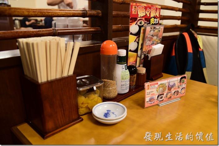日本-街角屋平價和食定食料理。【街角屋(街かど屋)】的桌上有很多的佐料,有白芝麻可以加在白飯上、醃蘿蔔、日式醬油。