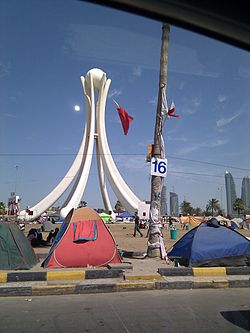"The 2011–2012 Bahraini uprising, sometimes called the February 14 Revolution was  a sustained campaign of civil resistance. As part of the revolutionary wave of protests in the Middle East and North Africa, the Bahraini protests were initially aimed at achieving greater political freedom and equality for the majority Shia population and expanded to a call to end the monarchy of King Hamad following a deadly night raid on 17 February 2011 against protesters at the Pearl Roundabout in Manama, known as Bloody Thursday.  Protesters in Manama camped out for days at the Pearl Roundabout, which functioned as the centre point of protests there. After a month, the government requested troops and police from the Saudi Arabia and UAE. The response has been described as a ""brutal"". The police carried out midnight house raids in Shia neighborhoods, beatings at checkpoints, and denial of medical care in a campaign of intimidation. More than 2,929 people have been arrested. (photo-(persephonemagazine.com)"