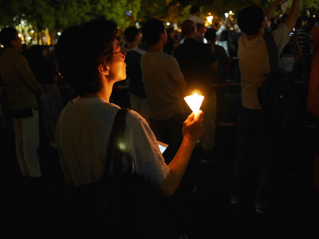 person holding a candle at a vigil in Victoria Park, Hong Kong, commemorating the anniversary of the Tiananmen Square crackdown