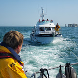 Poole ALB Crew Members Joe Manning (onboard the ALB) and Scott Rowland (onboard the casualty vessel) monitoring the tow en route back inot Poole Harbour. 22 August 2013 Photo credit: RNLI/Anne Millman