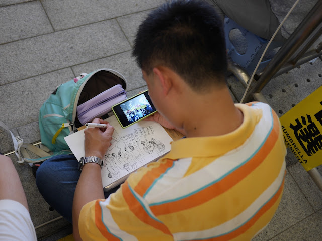 man drawing a copy of a photo on a mobile phone