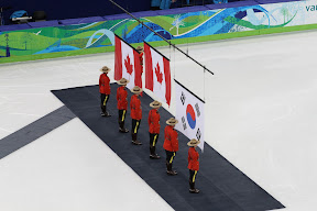 Flags being raised during O Canada for the men's 500m short track medal ceremony