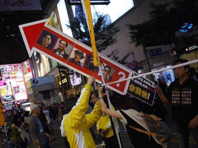 Sign with photos of the five people missing from Causeway Bay Books