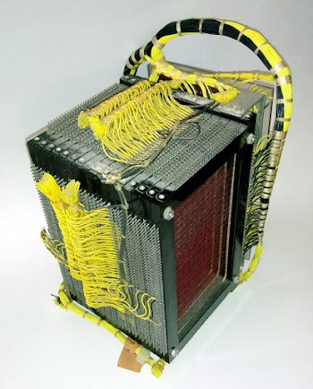 The 4000 character core memory module from an IBM 1401 computer. Tiny ferrite cores are strung on the red wires.