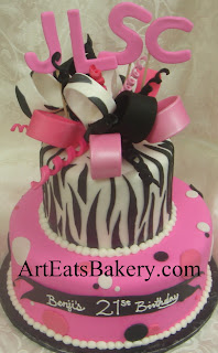 Two tier black, white and pink fondant animal print and polka dot unique creative girl's or lady's birthday cake design idea with zebra bow and monogram topper