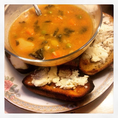small bowl of vegetable curry soup with plate of toasted french bread and goat cheese