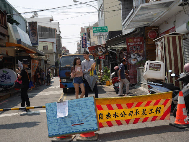 young couple walking by a sign for construction work by the Taiwan Water Corporation at Zhengxing Street in Tainan