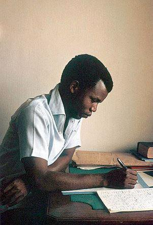 Chinua Achebe writing at his office in Enugu in 1959