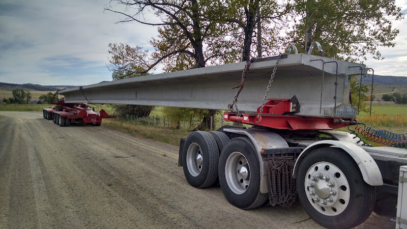 flatbed trailer and dolly loaded with oversized cement bridge beams