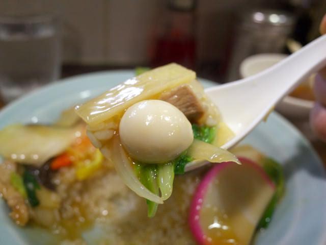 レンゲですくった中華丼。うずらの玉子とタケノコが乗ってる。