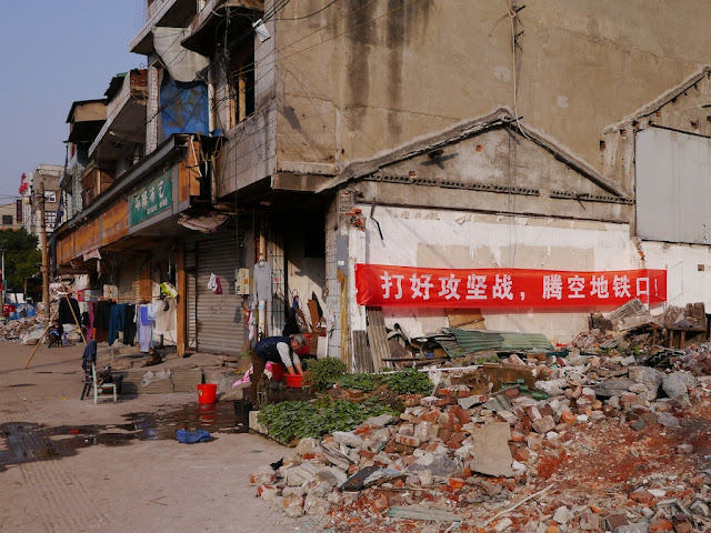 "red banner reading ""打好攻坚战,腾空地铁口"" hung on a remaining building at Beizheng Street in Changsha"