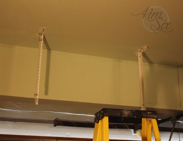 Installing brackets from ceiling for storage rack