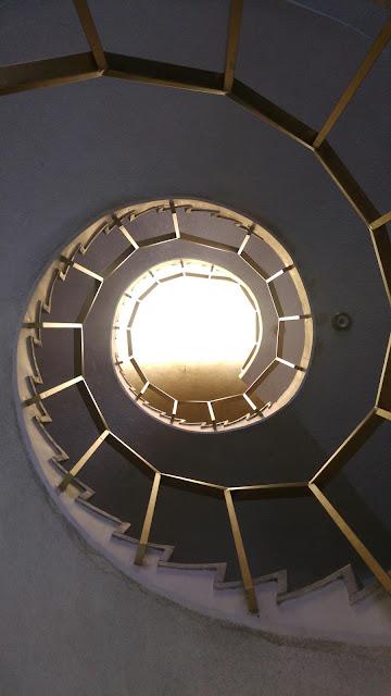 Foto de escaleras en espiral que asemejan alcanzar la luz en el cielo